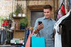 Gelukkige jonge en mens die online terwijl het winkelen glimlachen babbelen royalty-vrije stock fotografie