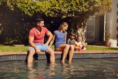 Gelukkige jonge familie die dichtbij pool genieten van stock foto's