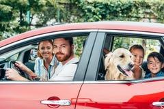 gelukkige jonge familie die door auto reizen royalty-vrije stock afbeelding