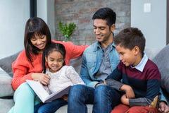 Gelukkige jonge familie die een boek samen lezen stock fotografie