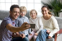 Gelukkige jonge familie die met goedgekeurde jonge geitjes het nemen glimlachen selfie toget Royalty-vrije Stock Foto's
