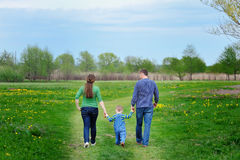 Gelukkige jonge familie die onderaan de weg buiten in groene aard lopen Royalty-vrije Stock Foto