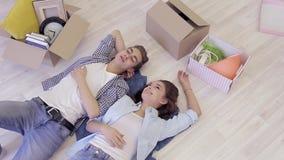 Gelukkige jonge familie die op de vloer onder de dozen tijdens verhuizing liggen stock footage