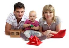 Gelukkige jonge familie die op de vloer op rode kussens liggen Stock Afbeeldingen