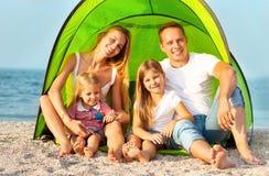 Gelukkige jonge familie die op het strand kamperen royalty-vrije stock foto's
