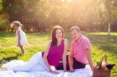 Gelukkige jonge familie die picknick hebben bij weide stock foto's