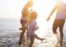 Gelukkige jonge familie die pret hebben die op strand bij zonsondergang lopen royalty-vrije stock foto's