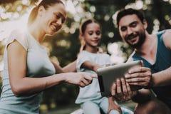Gelukkige Jonge Familie die Tablet in de Zomerpark gebruiken stock afbeelding