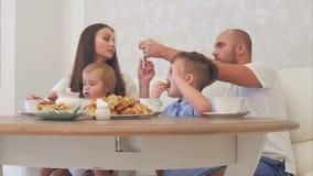 Gelukkige jonge familie die van thee met snoepjes genieten bij restaurant of koffie of huis stock video