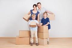 Gelukkige jonge familie dragende dozen Stock Fotografie