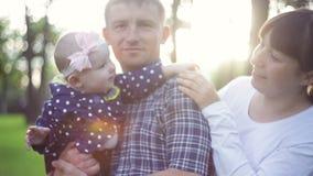 Gelukkige jonge familie het besteden tijd samen buiten in groen de zomerpark stock footage