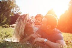 Gelukkige jonge familie het besteden tijd samen buiten in groene aard Stock Afbeelding