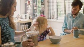 Gelukkige jonge familie: mamma, papa en hun dochter die ontbijt hebben bij de keukenlijst Langzame motie, Steadicam-schot stock videobeelden