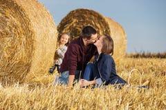 Gelukkige jonge familie met 2 éénjarigenmeisje naast hooibalen stock afbeeldingen
