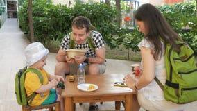 Gelukkige jonge familie met een baby die op openlucht in een koffie eten Iedereen zit op kleine houten stoelen stock video