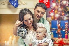Gelukkige jonge familie met een kind dichtbij de Kerstboom stock foto's