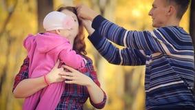 Gelukkige jonge familie met pasgeboren in de herfstpark stock video