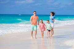 Gelukkige jonge familie met twee jonge geitjes op een tropisch strand Stock Fotografie