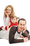 Gelukkige jonge familie samen in studio Stock Afbeeldingen