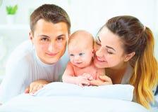 Gelukkige jonge familie Vader, moeder en hun pasgeboren baby stock afbeeldingen