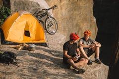 gelukkige jonge fietsreizigers met ingeblikte voedselzitting royalty-vrije stock fotografie