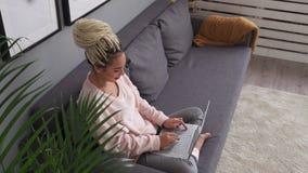 Gelukkige jonge freelancervrouw die aan laptop computer op comfortabele laag werken stock video