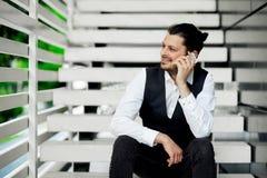 Gelukkige jonge gebaarde mens die op de het mobiele telefoon en glimlachen spreken Royalty-vrije Stock Foto