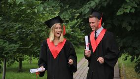 Gelukkige jonge gediplomeerden die en graduatie in park vieren dichtbij academie dansen stock videobeelden