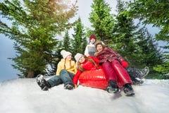 Gelukkige jonge geitjes die onderaan de heuvel op rode ice-boat berijden Royalty-vrije Stock Fotografie