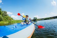 Gelukkige jonge geitjes die op de rivier op een zonnige dag tijdens de zomervakantie kayaking stock foto's