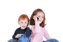 Gelukkige jonge geitjes die op mobiele telefoons spreken stock afbeeldingen
