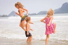 Gelukkige jonge geitjes die op strand spelen Stock Foto