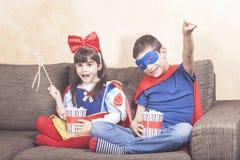 Gelukkige jonge geitjes die op TV thuis letten Stock Afbeeldingen