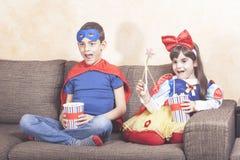 Gelukkige jonge geitjes die op TV thuis letten Stock Foto's