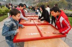 Gelukkige jonge geitjes die raadsspel op de speelplaats van Tbilisoba-festival spelen Royalty-vrije Stock Foto's