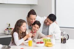 Gelukkige jonge geitjes die van ontbijt met ouders in keuken genieten stock afbeelding