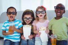 Gelukkige jonge geitjes die van popcorn en dranken genieten terwijl het zitten royalty-vrije stock afbeeldingen