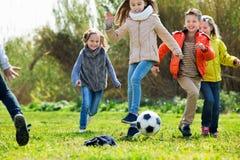 Gelukkige jonge geitjes die voetbal in openlucht spelen Royalty-vrije Stock Foto's