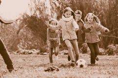 Gelukkige jonge geitjes die voetbal in openlucht spelen stock foto's