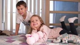 Gelukkige jonge geitjes die in witte slaapkamer spelen Weinig jongen en meisje, broer en de zuster spelen op het bed die pyjama's stock video