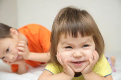 Gelukkige jonge geitjes, glimlachend meisje met leuke wangen en haar broer royalty-vrije stock fotografie