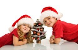 Gelukkige jonge geitjes met kleine Kerstmisboom Royalty-vrije Stock Foto's
