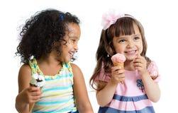 Gelukkige jonge geitjes twee meisjes die geïsoleerd roomijs eten Stock Fotografie
