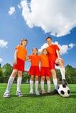 Gelukkige jonge geitjes van verschillende hoogte met voetbal stock afbeelding
