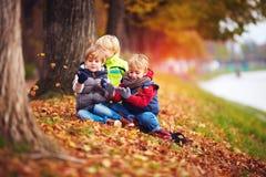 Gelukkige jonge geitjes, vrienden die pret onder gevallen bladeren in de herfstpark hebben stock foto