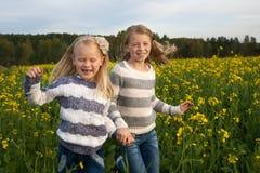 Gelukkige jonge geitjeszusters die rond binnen het lachen lopen Stock Fotografie