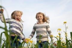 Gelukkige jonge geitjeszusters die rond binnen het lachen lopen Stock Afbeelding