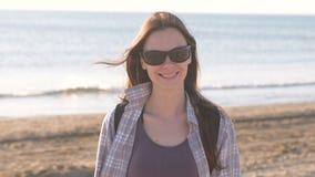 Gelukkige jonge glimlachende donkerbruine vrouw in zonnebril bij zandstrand door het overzees stock footage
