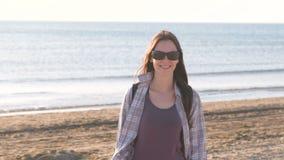 Gelukkige jonge glimlachende donkerbruine vrouw in zonnebril bij zandstrand door het overzees stock videobeelden