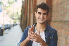 Gelukkige jonge glimlachende mens die handen slaan royalty-vrije stock foto's